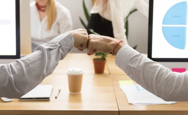 workers-fist-bumping-because-of-improve-to-company-culture